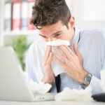 Man at desk blowing nose in tissue: MaxFilings Business Management Blog