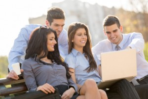Group of young business people looking at laptop: MaxFilings Interviews & Advice Blog