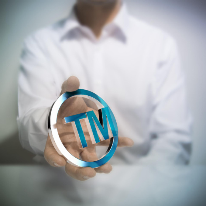 Man with trademark symbol in hand: MaxFilings Patents and Trademarks Blog