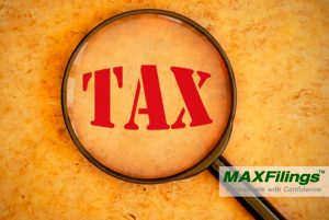 "magnifying glass on word ""TAX"""